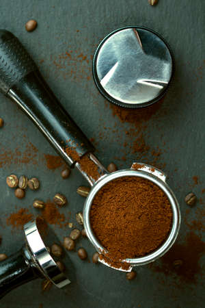 Portafilter with coffee bean and temper on concrete table Standard-Bild