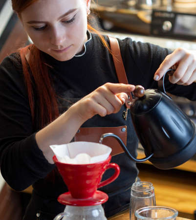 Barista pouring boiling water of manual drip brewer and make coffee. Girl pouring on coffee ground with filter. Alternative pure over method. Standard-Bild