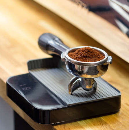 Portafilter on the scales with freshly ground morning coffee on wood table