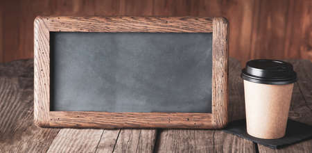 vintage slate chalk board and coffee paper cup with on grunge wood table Standard-Bild