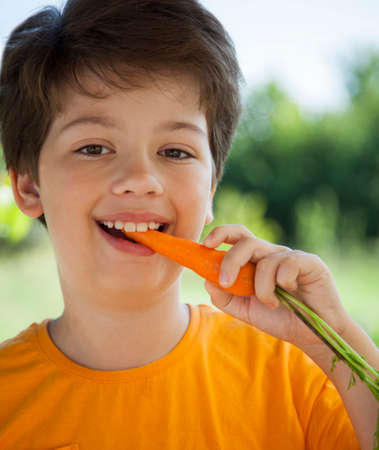 Happy boy biting the carrot, A child with a vegetable. Kid eating fresh carrots