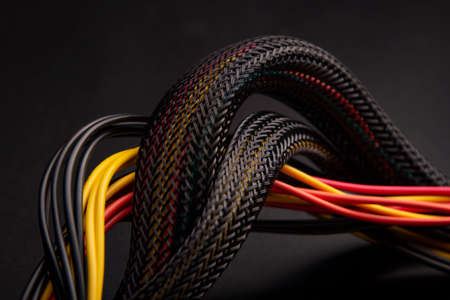 Black Cable with snake skin. Black braided wires in bundle on black background. Braided Sleeving. Data line protection. Wire Flame-retardant nylon tube