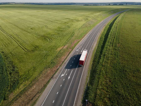 White Truck with Cargo Semi Trailer Moving on Road in Direction. Aerial top view Standard-Bild