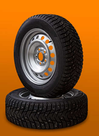 Car wheel and winter studded tire on orange background