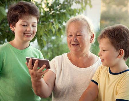 cute little boy using smartphone with grandma at home veranda.