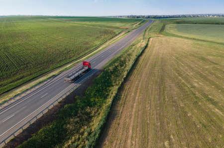 Red tipper truck on street road highway transportation. Semi-truck countryside aerial view. Standard-Bild