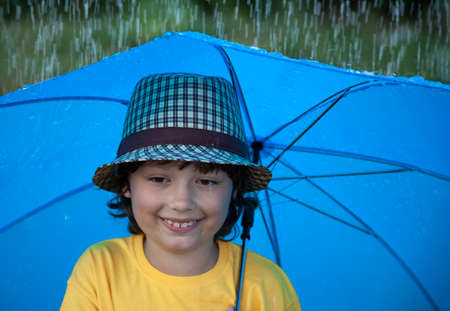 child with an umbrella walks in the rain, happy boy with umbrella outdoors