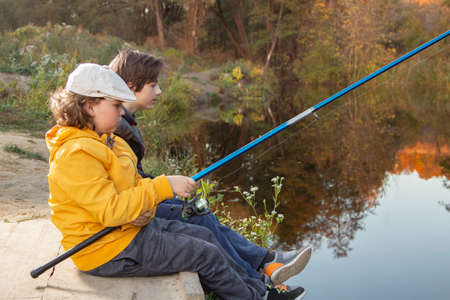 Happy teen boys go fishing on the river, two children of the fisherman with a fishing rod on the shore of the river Standard-Bild