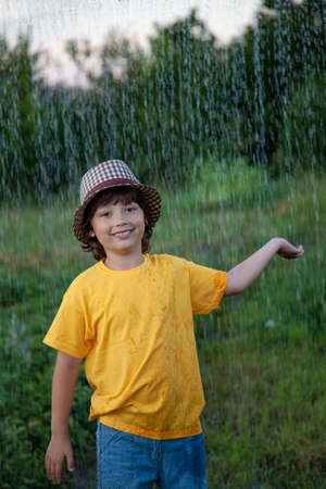Child playing outdoor on rainy day. Happy boy in summer rain