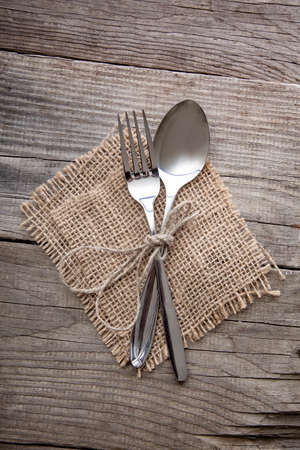 Fork and Spoon on old wooden table napkin and burlap, grunge rustic style, top view. Standard-Bild