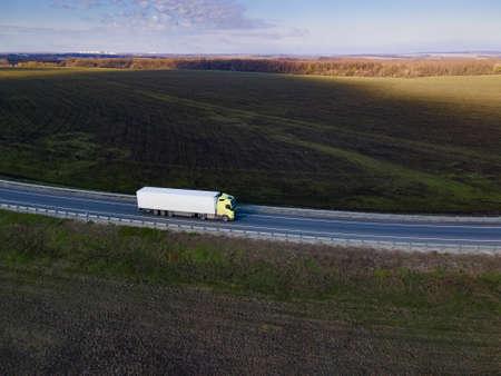 White Truck with Cargo Semi Trailer Moving on Summer Road. Standard-Bild