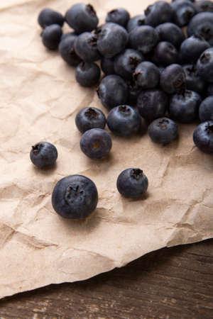 Heap ripe sweet blueberries on rustic paper top view
