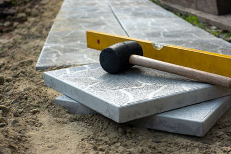 Laying a paving stone or brick. Gray concrete slabs in house courtyard on sand foundation base.