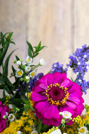 Zinnia flowers and other flowers in a beautiful bouquet on old grunge wooden background (Erígeron)