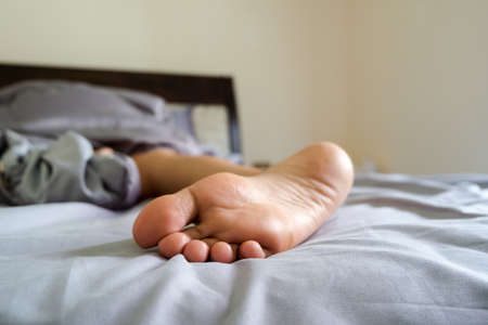 Close-up woman foot, Woman is lying on bed under blanket.