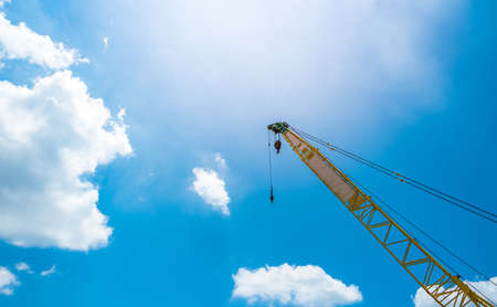 Mobile construction crane against sunlight and clear blue sky.