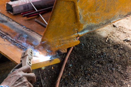 Worker welding the iron for fix wheel loader.