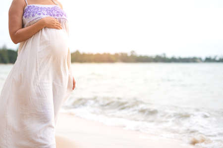 Happy and beautiful pregnant woman standing on beach hand touching on her belly. Expectant mother wear white tunic having fun in summer vacation for relaxation. Pregnancy healthy and travel concept. Фото со стока