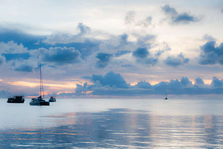 Soft focus of boats in the middle of sea suface amidst dark clouds at sunset.