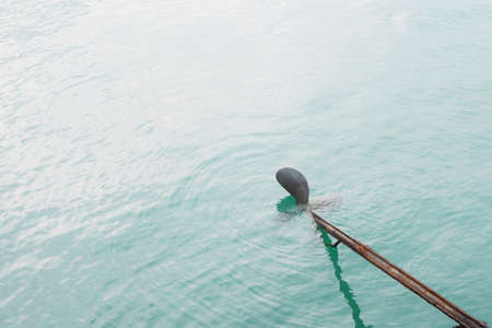 Close up of long tail boat propeller in water.
