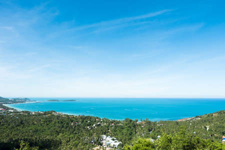 Sea view at Chaweng beach in Koh Samui, Thailand. The scenery of seascape and bay with city and forest of coconut trees in aerial view on summer day.