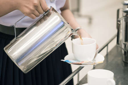 Close up woman staff is pouring coffee in pot to serve guests attending seminar during break time in meeting room.