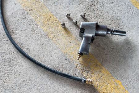 Air impact  wrench and bolts on the floor. Stock Photo