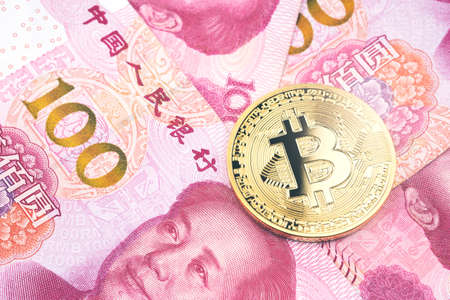 Golden bitcoin on pile of one hundred Chinese yuan banknotes background. Cryptocurrency, digital currency with yuan money bills. Фото со стока