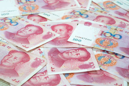 Pile of many one hundred Chinese yuan banknotes on table, Chinas currency  background in concept of financial and business. 版權商用圖片