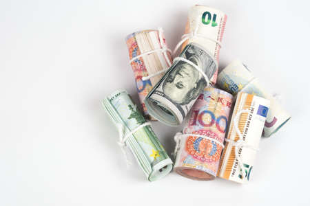 Currencies and money exchange trading concepts. The rolls of different currencies US Dollar, Euro and Chinese yuan banknotes with white rope band isolated on white background.