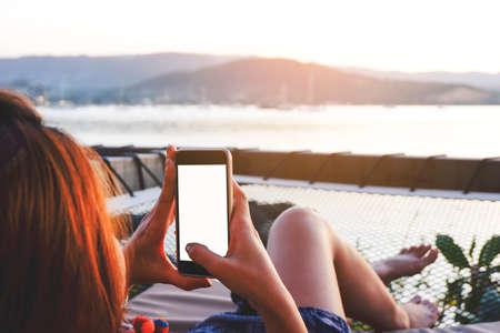 Young woman using black smartphone with blank desktop screen while lying side the sea with evening sunset background. Mockup image of woman hand holding phone chatting online message with friends.