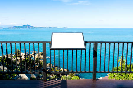 Blank advertising billboard on steel fence over calm blue sea and sky background at tropical island. Outdoor sign panel can advertisement for display, guide map, food menu and travel information. Stockfoto