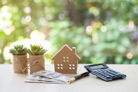 Home Loan, mortgage and real estate concept, House model with pile of dollar bills, calculator, pen and plant pots on table with garden background for business, finance, banking, and saving money. Archivio Fotografico