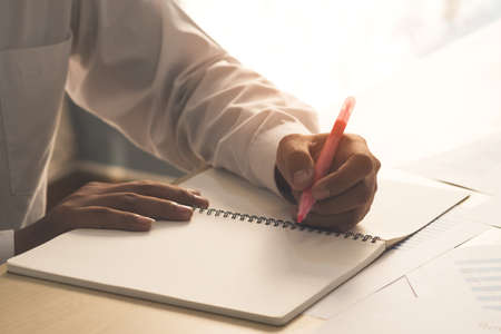 Success businessman hand holding pink marker pen on hand and writing idea or somethings on notebook with business paper on wooden table in home and office. Business and Education concept.