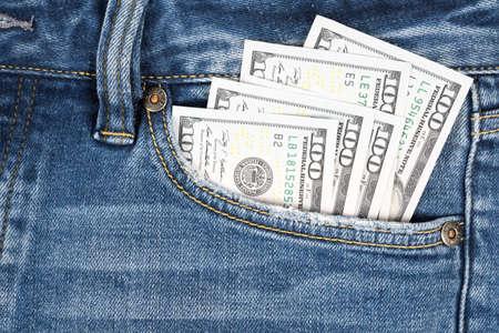 Money in pocket of blue jean. One hundred dollar bills in back of jean pocket.