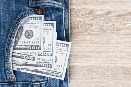 Money in pocket of blue jean on wooden background with copy space. One hundred dollar bills in back of jean pocket. 스톡 콘텐츠