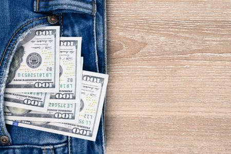 Money in pocket of blue jean on wooden background with copy space. One hundred dollar bills in back of jean pocket. Standard-Bild