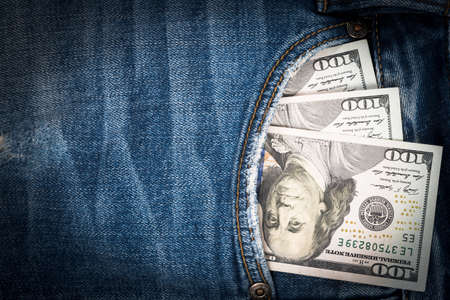 Money in pocket of blue jean with copy space. One hundred dollar bills in back jean pocket. 版權商用圖片