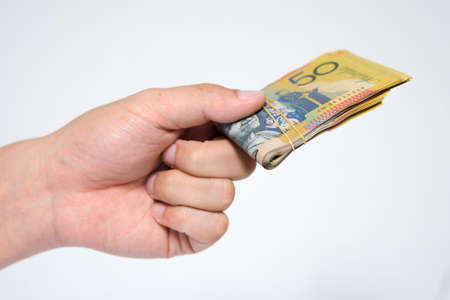 Close up  fifty Australia Dollar money bills in hand isolated on white background. Hand holding or giving money in financial and economy concepts.