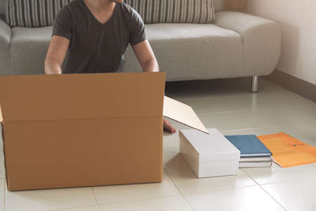 Young asian man packing and putting stuff in big cardboard box for moving to new home. House moving and house hunting concepts.