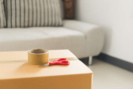 Packing cardboard box with scotch tape and red scissor in room. House moving concept. Standard-Bild