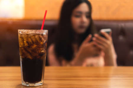 Close up glass of soft drink  carbonated with ice on wooden table with blurred of young asian woman using smartphone while sitting on luxury brown leather sofa waiting for food in restaurant. 版權商用圖片