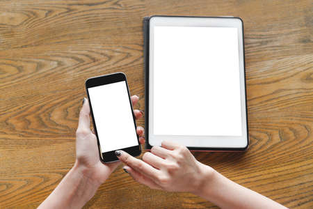 Mock up image woman hand using smartphone and digital tablet pc with blank white screen on wooden table in cafe for your advertising, top view. Business woman using multi devices for working at home.