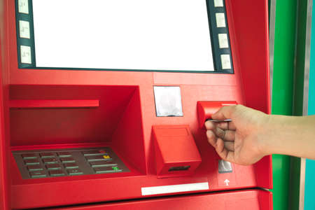 Man hand inserting debit or credit card to withdraw money with blank white screen ATM machine. Selective focus on hand with credit card using Automatic Teller Machine. Banking and financial concept. 스톡 콘텐츠