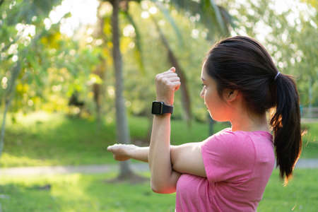 Young asian fitness woman stretching arms, tricep and shoulders before and after exercise in park at morning. Healthy female in sportswear warming up outdoor garden. Healthy and lifestyle concept.