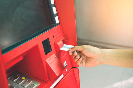 Man hand inserting debit or credit card to withdraw money with blank screen ATM machine. Selective focus on hand with credit card using Automatic Teller Machine. Banking and financial concept. Banque d'images