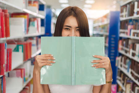 Portrait young asian woman hand holding book and hiding behind open book and looking at you in library on morning. 스톡 콘텐츠