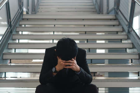 Young asian businessman sitting on stairs are stressing when he know business is failing and unemployed in office building. Depressed emotional after receiving bad news. Dismissed or deposed employee.