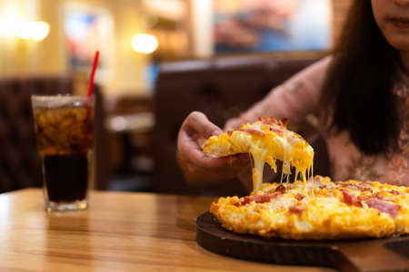 Slice of hot pizza with stringy cheese in hand. Young woman enjoy eating Hawaiian pizza topped with tomato sauce, cheese, pineapple and bacon on wooden board with soft drink in restaurant for dinner