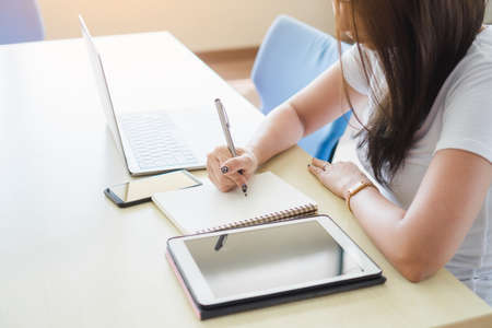 Beautiful asian business woman in casual working and writing her ideas on notebook with laptop and blank screen tablet, smartphone in modern office. Female freelance blogger plan to writing content.